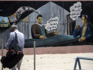 "A man walks past a mural painting with Arabic writing warning people not to work as agents for the Israeli intelligence on the Palestinian side of he Israeli border terminal of Erez in the Gaza strip on July 13, 2016. Arabic writing in a cartoon format on the wall painiting reads: ""How about working for us,""(R) an Israeli agent asks a Palestinian man (C) who replies: ""Palestinians will never be traitors."" / AFP / MAHMUD HAMS"