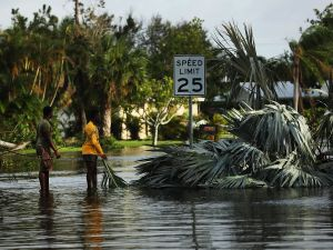 NAPLES, FL - SEPTEMBER 11: People walk through flooded streets the morning after Hurricane Irma swept through the area on September 11, 2017 in Naples, Florida. Hurricane Irma made another landfall near Naples yesterday after inundating the Florida Keys. Electricity was out in much of the region with localized flooding.