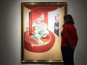 A Christie's employee poses with Study of a Red Pope, 1962. 2nd Version 1971 by Francis Bacon at Christie's.