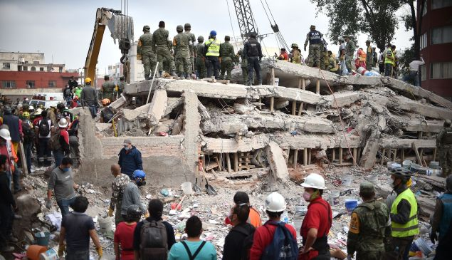 Rescuers, firefighters, policemen, soldiers and volunteers search for survivors in a flattened building in Mexico City.