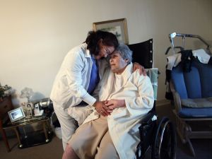 United HomeCare Services home health aide Wendy Cerrato hugs Olga Socarras as she helps her during a visit.