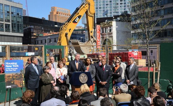 Flanked by elected officials and advocates, Mayor Bill de Blasio unveils his affordable housing plan at a press conference in May 2014.