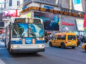 Blue-white bus driving in a prominent street in New York City.