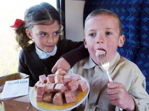 Seven year olds Caitlin Parker and Harry Knight try out Spam on their train journey to Okehampton Station. War evacuation history lesson