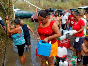People collect water from a natural spring created by the landslides in a mountain next to a road in Corozal, west of San Juan, Puerto Rico following the passage of Hurricane Maria.