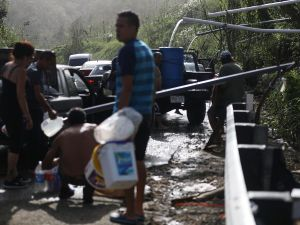 People fill containers with water funneled with pipes from a mountain stream nearly one month after Hurricane Maria struck on October 19, 2017 in Utuado, Puerto Rico.
