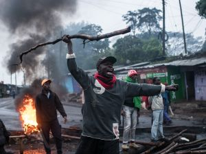 A protestor yells as nearby police officers approach in the Kibera slum on October 26, 2017 in Nairobi, Kenya.