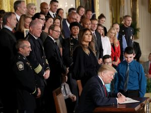 WASHINGTON, DC - OCTOBER 26: As, U.S. first lady Melania Trump looks on, U.S. President Donald Trump signs a presidential memorandum during an event highlighting efforts to battle the opioid crisis in the U.S. October 26, 2017 in Washington, DC. Trump plans to authorize the Department of Health and Human Services to declare a nationwide public health emergency in an effort to reduce the number of opioid overdose deaths across the nation.