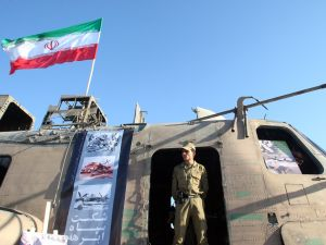 A member of Iran's elite Revolutionary Guard stands under a national flag on the wreckage of a captured US air force CH-53 Sea Stallion helicopter.