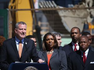 Mayor Bill de Blasio stands with Public Advocate Letitia James and Brooklyn Borough President Eric Adams while unveiling his affordable housing plan in Brooklyn in May 2014.