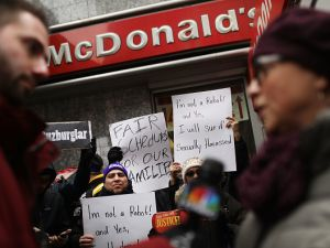 Protesters with NYC Fight for $15 gather in front of a McDonalds to rally against fast food executive Andrew Puzder, who is President Donald Trump's nomination to lead the Labor Department.