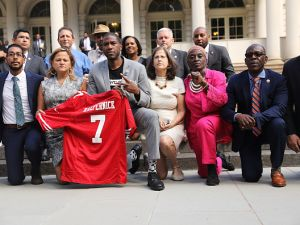 """Brooklyn Councilman Jumaane Williams, center, """"takes a knee"""" with other Council members at City Hall in support of former NFL quarterback Colin Kaepernick."""