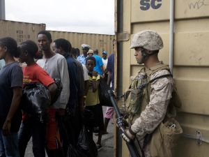 A US soldier (R) stands guard as Ethiopian and Somali refugees disembark from the US Navy ship the USS Pearl Harbor.