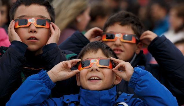 MADRID, SPAIN - MARCH 20: Children use protective glasses to look into the sky during a partial solar eclipse outside the Planetario on March 20, 2015 in Madrid.