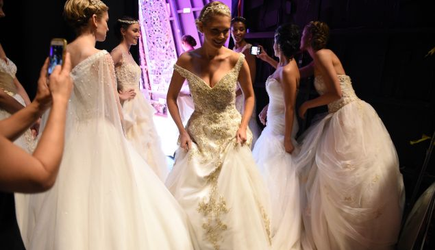Models prepare backstage during 2016 Alfred Angelo Disney Fairy Tale Weddings Bridal Collection fashion show debut.