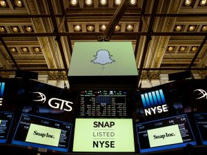 Signage for Snap Inc., parent company of Snapchat, is displayed on monitors on the floor New York Stock Exchange (NYSE) in New York City.