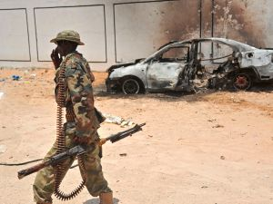 A Somali soldier patrols next to the burnt-out wreckage of a car that was used by suspected al Shabab fighters.