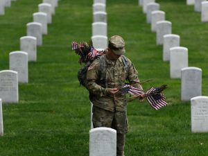 A member of the US Army places an American flags on a grave at Arlington National Cemetery on May 25, 2017 in Arlington, Va. in preparation for Memorial Day.