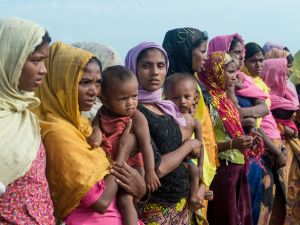 Women hold children at a makeshift camp in Rakhine state in Myanmar, where hundreds of Rohingya Muslims wait before crossing into Bangladesh, on November 12, 2017.