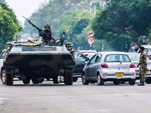 An armored personnel carrier stations by an intersection as Zimbabwean soldiers regulate traffic in Harare on November 15, 2017.