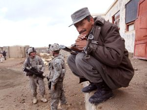 A police officer with the Afghan National Police (ANP) stands guard with U.S. soldiers in Sar Hawza, Afghanistan.