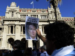 A man holds a portrait of late Argentine prosecutor Alberto Nisman during a demonstration in demand of justice, in front of the law court in Buenos Aires on March 18, 2015. Nisman was found death in his flat with a bullet through his head on January 18, the day before he was to go before a congressional hearing to air his finding that Argentine President Cristina Fernandez de Kirchner and her foreign minister plotted to shield Iranian officials implicated in the bombing of the AMIA Jewish-Argentine charity. AFP PHOTO / JUAN MABROMATA (Photo credit should read )