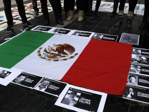 Portraits of Mexican journalist Javier Valdez, murdered in Mexico, were placed on a Mexican flag during a protest in front of Argentina's Foreign Office Ministry in Buenos Aires in May.