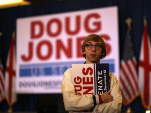 BIRMINGHAM, AL - DECEMBER 12: A supporter of democratic U.S. Senatorial candidate Doug Jones holds a sign as he watches election returns during an election night gathering the Sheraton Hotel on December 12, 2017 in Birmingham, Alabama. Doug Jones is in a tight race with republican challenger Roy Moore to fill the Attorney General Jeff Session's seat.