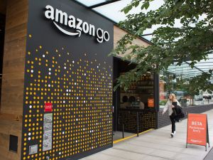A woman walks past the Amazon Go grocery store at the Amazon corporate headquarters on June 16, 2017 in Seattle, Washington.