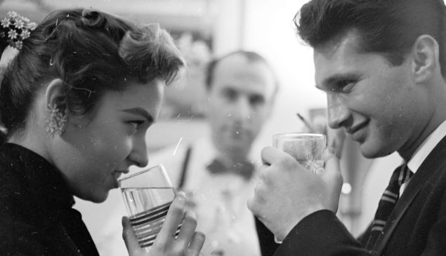 circa 1955: A bartender waits attentively on a young couple out on a date.