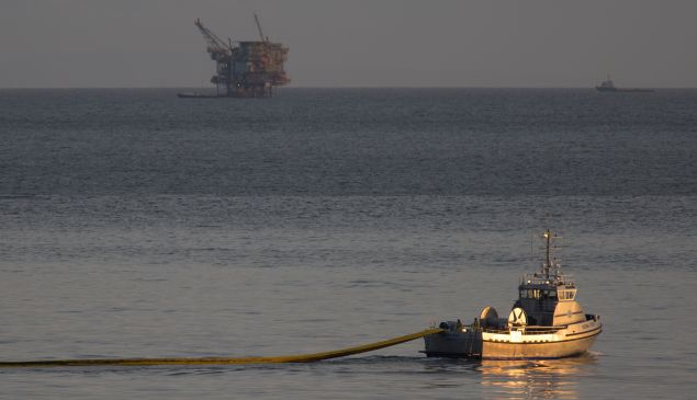 A boat with the nonprofit collective Clean Seas deploys a boom, with an oil platform seen in the distance, to try to contain an oil spill on May 19, 2015 north of Goleta, California.