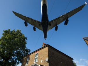 A passenger aircraft passes over a residential house as it prepares to land at London Heathrow Airport in west London on October 17, 2016.