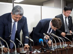Former CEO of collapsed Bitcoin exchange Mt. Gox bows with his lawyers at the end of a press conference held after his first hearing in Tokyo on July 11, 2017.