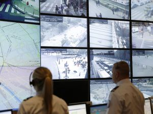 Police officers monitor control screens.