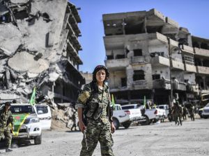Kurdish female fighters of the Syrian Democratic Forces (SDF) gather during a celebration at the iconic Al-Naim square in Raqa on October 19, 2017, after retaking the city from Islamic State (IS) group fighters.