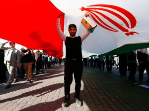 A pro-government demonstrator stands under an Iranian flag during a march in Iran's southwestern city of Ahvaz on January 3, 2018, as tens of thousands gathered across Iran in a massive show of strength for the Islamic rulers after days of deadly unrest. / AFP PHOTO / TASNIM NEWS / MORTEZA JABERIAN (Photo credit should read )