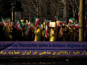 "Protesters hold flags of the National Council of Resistance of Iran (NCRI) next to a banner reading ""We support the insurrection against the religious dictatorship in Iran"" during a demonstration in support of the Iranian people amid a wave of protests spreading throughout Iran, on January 3, 2018, in Paris."
