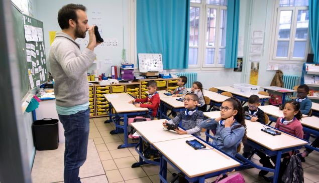 Schoolchildren listen to a teacher showing how to use a digital tablet in a primary school in Marseille, France.