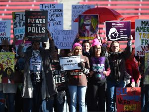 "Attendees hold signs onstage during the Women's March ""Power to the Polls"" voter registration tour launch at on January 21, 2018 in Las Vegas, Nevada."