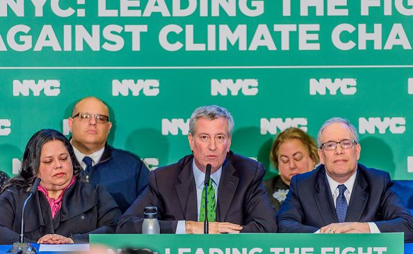 Mayor Bill de Blasio, center, announces a goal to divest from fossil fuel reserve owners within five years at a press conference in Lower Manhattan on Jan. 10, 2018.