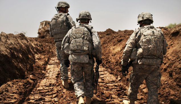 U.S. soldiers with the 3rd Armored Cavalry Regiment patrol a new ditch they have dug to protect the base from attack on July 19, 2011 in Iskandariya, Babil Province Iraq.