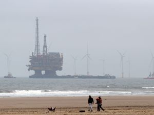 Shell's Brent Delta Topside offshore oil drilling rig platform is towed by tug boats along the coastline .