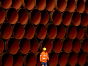 A worker stands in front of pipes at the Nord Stream 2 facility at Mukran on Ruegen Islandon October 19, 2017 in Sassnitz, Germany.