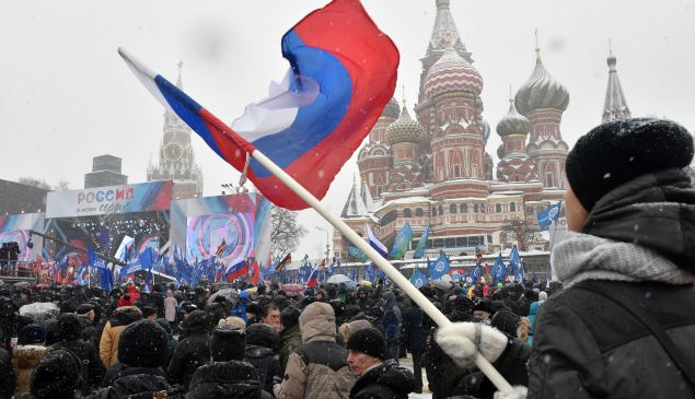 A man holds a national flag during the 'Russia is in my heart!' rally in support of Russian athletes on February 3, 2018.