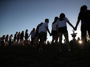 Students and family members holds hands around a memorial in front of Marjory Stoneman Douglas High School where 17 people were killed in Parkland, Fla.