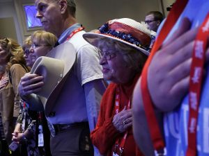 Attendees listen to the national anthem during CPAC 2018.
