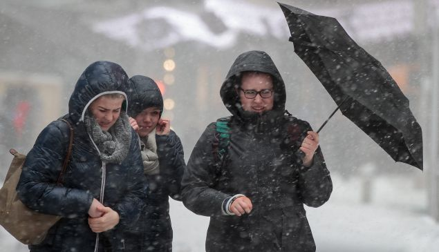 A group of women cross the street in the wind and snow.