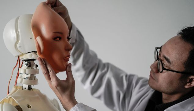 """This photo taken on February 1, 2018 shows an engineer holding a silicon face against the head of a robot at a lab of a doll factory of EXDOLL, a firm based in the northeastern Chinese port city of Dalian. With China facing a massive gender gap and a greying population, a company wants to hook up lonely men and retirees with a new kind of companion: """"Smart"""" sex dolls that can talk, play music and turn on dishwashers."""
