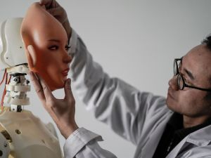 "This photo taken on February 1, 2018 shows an engineer holding a silicon face against the head of a robot at a lab of a doll factory of EXDOLL, a firm based in the northeastern Chinese port city of Dalian. With China facing a massive gender gap and a greying population, a company wants to hook up lonely men and retirees with a new kind of companion: ""Smart"" sex dolls that can talk, play music and turn on dishwashers."
