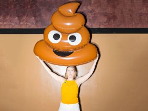 A woman holds the poop emoji at Emojicon in Brooklyn, New York